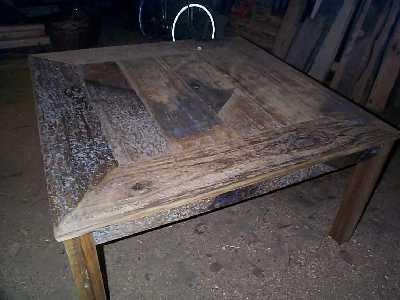 Tafel gemaakt van oud hout (iroko) wat gebruikt is alssluisdeur in een